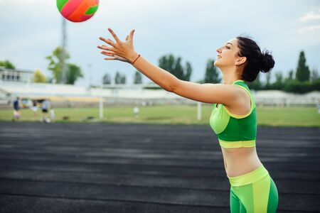 Beautiful curly girl flexing muscles in the stadium. Warm up with the ball. The girl goes in for sports. Light green tracksuit. Horizontal photo.