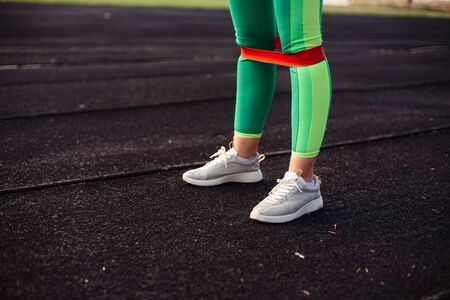 Legs of a girl in light green leggings with a pink rubber band for training