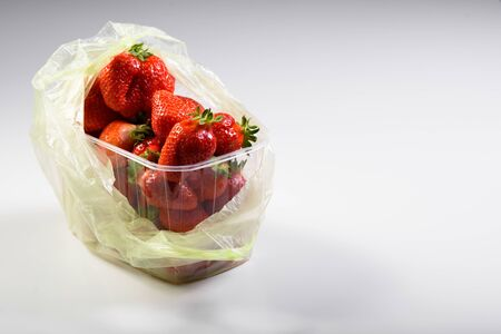 organic strawberries in a plastic box and bags. delivery of organic products. natural strawberry packaging.