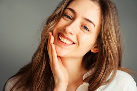 Close-up portrait of a smiling young girl in a white shirt on a gray background. Hands near the face. without retouching and makeup.