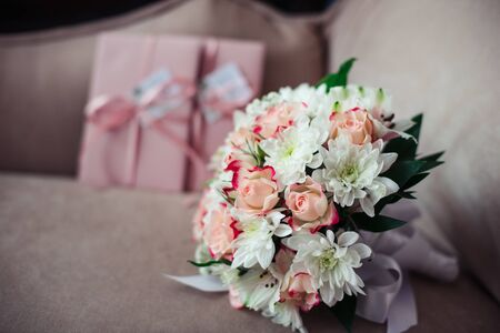 Wedding bouquet of roses and chrysanthemums on a background of pink certificates on a powdery sofa