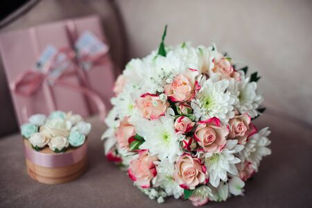 Close-up of a Wedding bouquet of pink roses and white chrysanthemums on a background of pink certificates. a box for rings on a powdery sofa