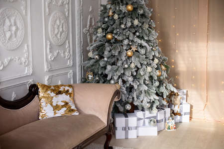 Festive Christmas living room or studio interior with a snowy Christmas tree, white gift boxes and a sofa. Imagens