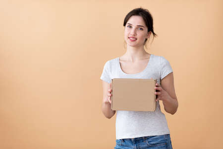 smiling girl bowing her head shows a box on a beige background. free space for an inscription