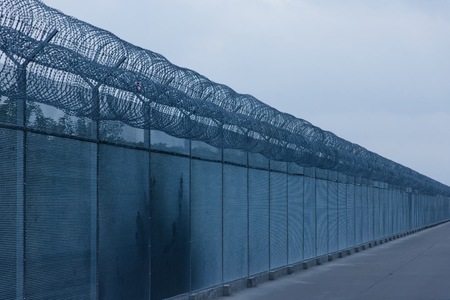 hopelessness: Security fence with a barbed wire with grey sky Stock Photo