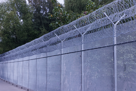 grey  sky: Security fence with a barbed wire with grey sky Stock Photo
