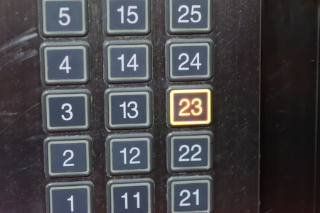 go inside: Elevator button with number 23 pushed Stock Photo