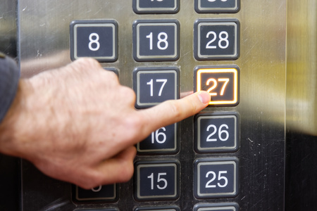 27: 27 twenty seven floor elevator button with light and pushing finger Stock Photo