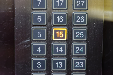 go inside: Elevator button with number 15 pushed Stock Photo