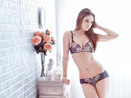 sexy young woman in lingerie posing near decorate brick wall with flowers  Soft light and colours photo