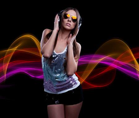 young DJ woman enjoying the music in the headphones photo