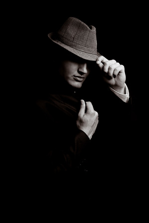 low key portrait of young gangster with hat in the darkness  Sepia toning  photo