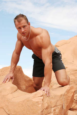 Sexy muscular man climbing red rocks Stock Photo