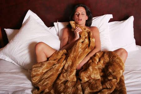 Sexy rijpe vrouw in bed Stockfoto