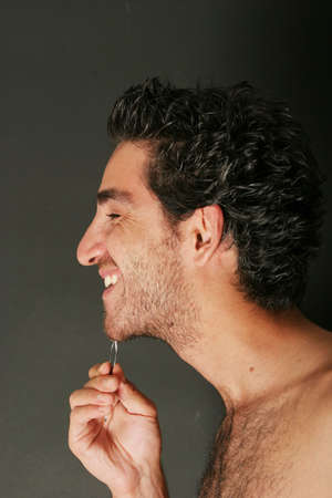 Handsome young man pulling his beard with tweezers photo