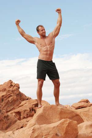 defined: Uomo muscolare sulle roccie rosse Archivio Fotografico