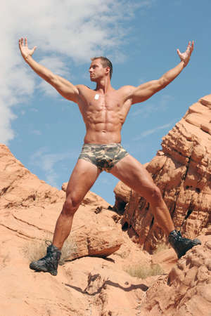 Sexy muscular man on red rocks Stock Photo
