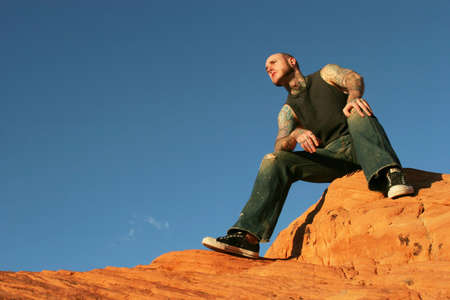 nosering: Tattoo man sitting on red rocks Stock Photo