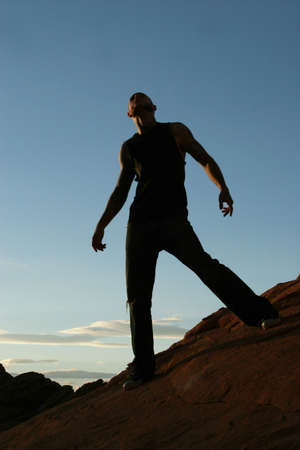 Silhouette of a man standing on mountain top photo
