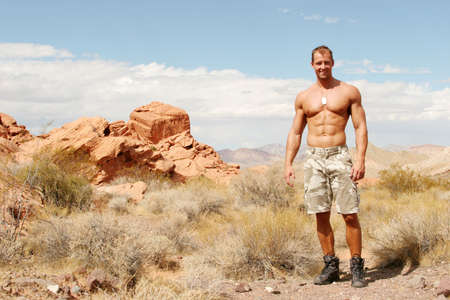 Muscular man on red rocks photo