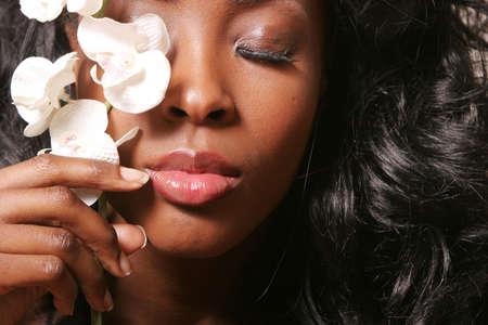 hair spa: Hermosa mujer negro que cubre sus ojos con blanco orqu�dea