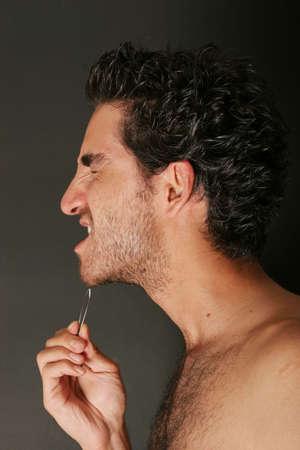 pinzas: Hermoso joven tirando de su barba con pinzas  Foto de archivo