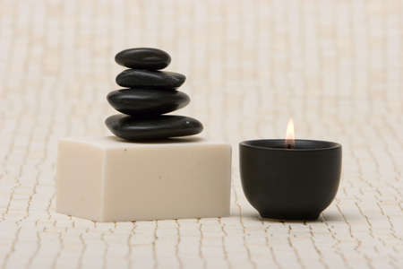 rejuvenate: Spa stones and a bar of soap with lit candle