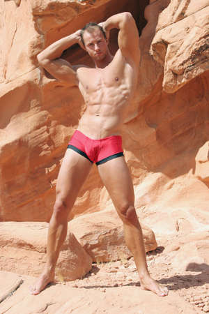 sexy muscular man: Sexy muscular man on red rocks Stock Photo
