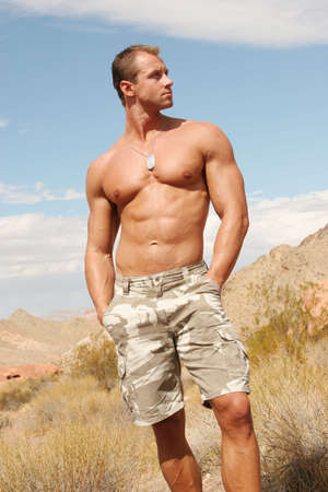 Handsome muscular man on red rocks photo