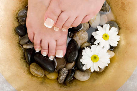 revitalize: Womans feet in bowl of water and rocks Stock Photo
