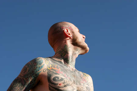 nosering: Man with tattoos against blue sky