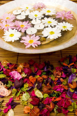 rejuvenate: White daisies and spa candles in water