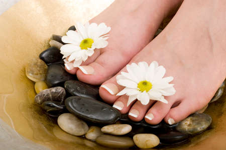 rejuvenate: Womans feet in bowl of water and rocks Stock Photo