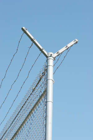 fencepost: Security fence on blue sky Stock Photo