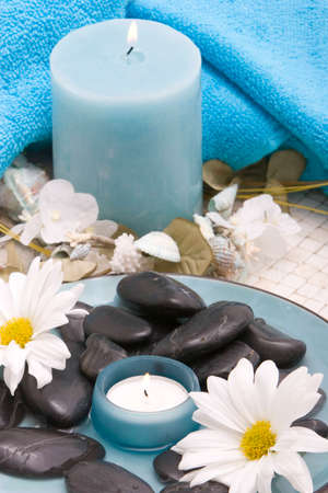 revitalize: Spa stones, candle and daisy
