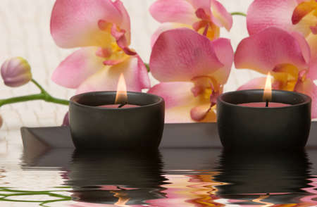 rejuvenate: Aromatherapy candles and pink orchid Stock Photo