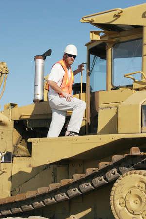 earthmover: Construction worker climbing on bulldozer Stock Photo