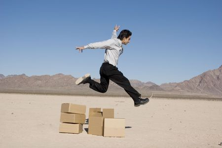 Businessman jumping over the boxes photo