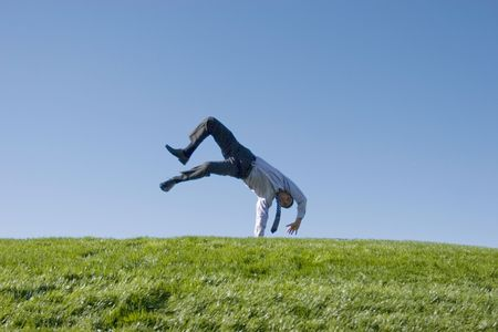 Happy businessman doing summersault on grass Stock Photo - 2065149