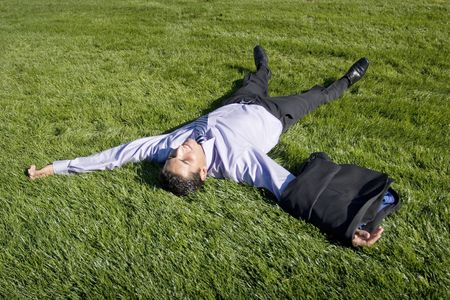 Businessman lying on green grass to relax Stock Photo - 2074724