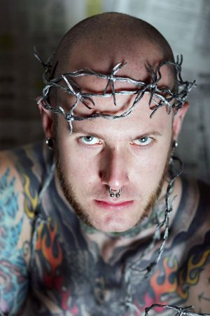Tattoo man with barbed wire around his head photo