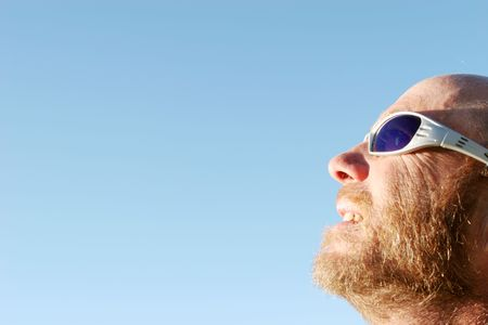 Man wearing sunglasses looking at the sun
