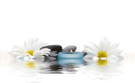 Massage stones, candle and daisies photo