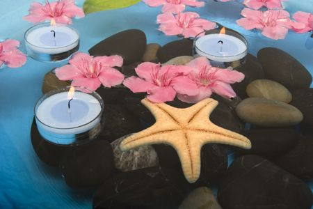 Flowers and candles floating in water Imagens