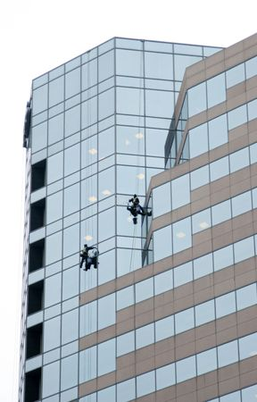 Window cleaners cleaning a tall skyscraper