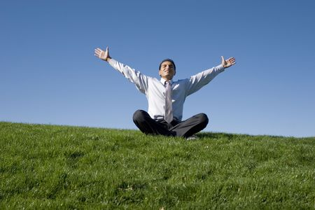 Businessman meditating on green grass photo