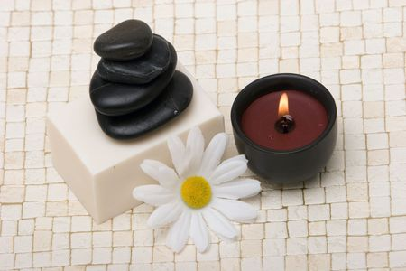 Spa stones, soap, lit candle and daisy Stock Photo - 2126760