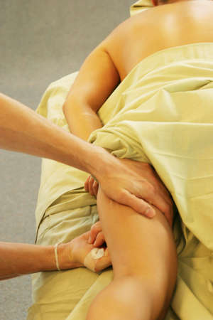 deeptissue: Massage therapist giving leg massage Stock Photo