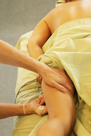 rejuvenate: Massage therapist giving leg massage Stock Photo