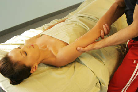 woman's: Massage therapist massaging womans arm Stock Photo